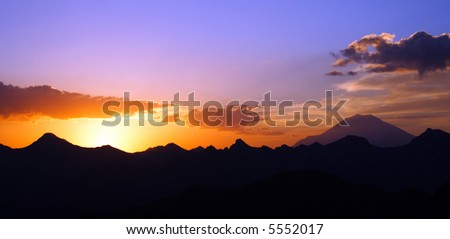 raising sun beams illuminating an Elbrus mountainside