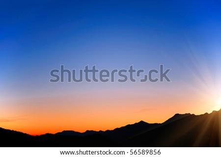 raising sun beams illuminating an  mountainside - stock photo