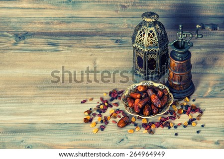 Raisins and dates on wooden background. Still life with vintage oriental lantern. Retro style toned picture - stock photo