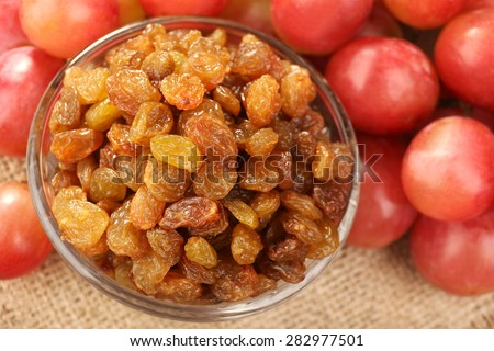 Raisins in bowl with grapes on table close up - stock photo