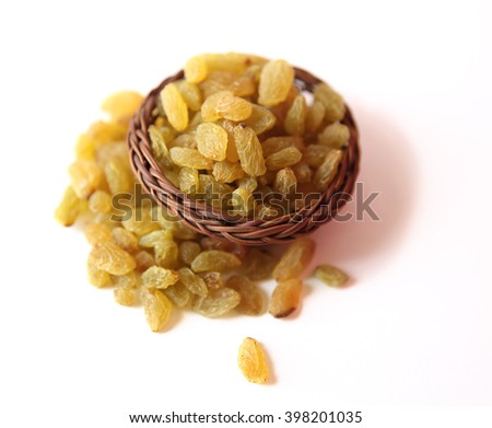 Raisins with wooden basket on a white background - stock photo
