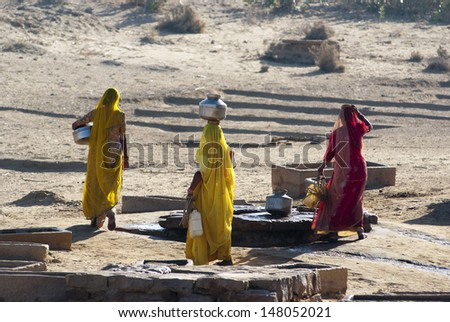 RAJASTHAN, INDIA - FEB 27: women lugging a water pot on their head on February 27, 2013 in Rajasthan, India. Due to the lack of piped water, poor tribals have to fetch water from its natural sources. - stock photo