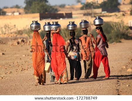 Rajasthan, India - February 27, 2013: women lugging a water pot on their head. Due to the lack of piped water, poor tribals have to fetch water from its natural sources. - stock photo