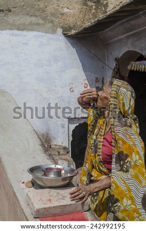 Rajasthan, India - March 29, 2014 - Old lady dressed in traditional dress taking care of hindu temple inside step wells