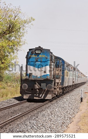 RAJASTHAN, INDIA - MARCH 9, 2015:  The Kolkata to Ahmedabad express passing through Rajasthan near the city of Pali. The journey takes 2 days and covers a distance of 1630 miles across 6 Indian states - stock photo