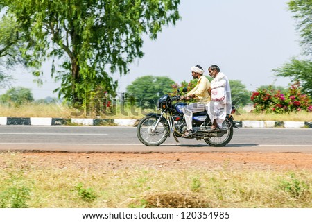 RAJASTHAN - INDIA - OCTOBER 18: men on scooter through busy highway street on October 18, 2012 in Rajasthan, India. Up to six family members manage to ride these two wheelers. - stock photo
