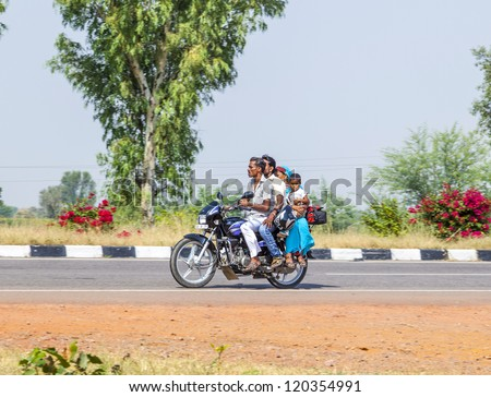 RAJASTHAN - INDIA - OCTOBER 18: Mother, father and small child ride on scooter on the highway on October 28, 2012 in Rajasthan, India. Up to six family members manage to ride these two wheelers. - stock photo