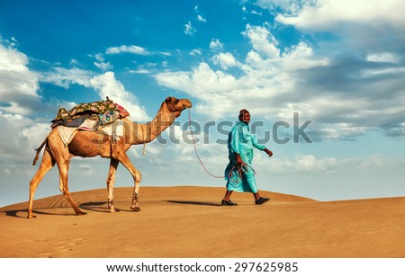 Rajasthan travel background - Indian cameleer (camel driver) with camels in dunes of Thar desert. Jaisalmer, Rajasthan, India - stock photo