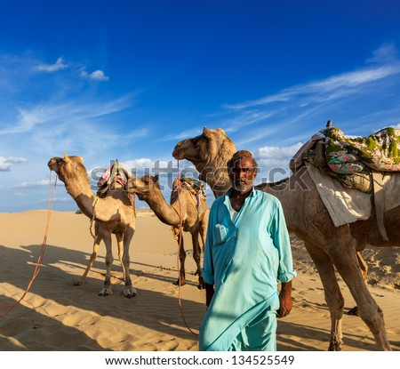 Rajasthan travel background - Indian man cameleer (camel driver) portrait with camels in dunes of Thar desert. Jaisalmer, Rajasthan, India - stock photo
