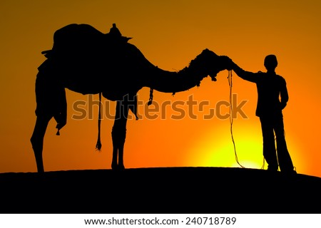 Rajasthan village. Silhouette of a man and camel at sunset in the desert, Jaisalmer - India - stock photo