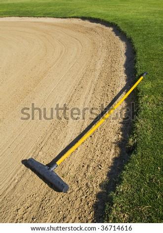 Rake in golf bunker - stock photo