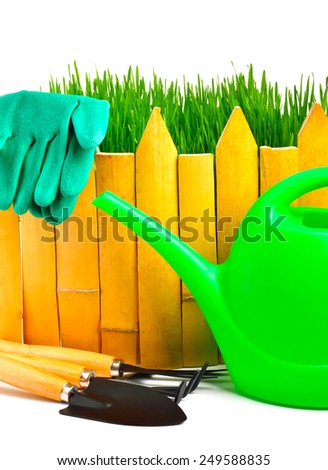 rake, shovel, rubber gloves, watering can against the wooden fence isolated on white - stock photo