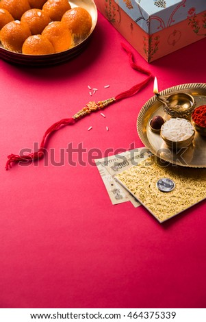 Rakhi and diya in a puja thali with gift box, indian currency notes, envelope and sweet motichur laddu