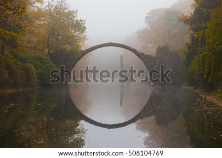 Rakotzbruecke (Devil's bridge) in early morning mist, in autumn, Kromlau, Germany