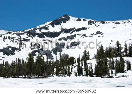 Ralston Peak in California near Lake Tahoe, mostly covered in snow and towering above a frozen lake, under a deep blue sky - stock photo