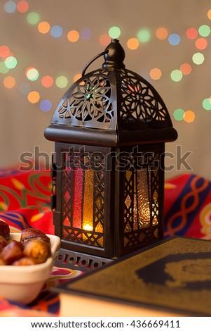 Ramadan Background - Lantern, dish of dates and Quraan on Ramadan colorful fabrics - stock photo