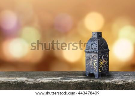Ramadan kareem lantern on grunge antique wood table floor w/ blur festive colorful gold candle light illumination pattern background: Islamic calendar muslim religious fasting month worldwide concept - stock photo