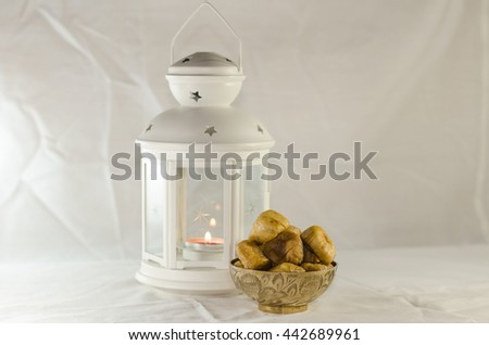 Ramadan Kareem Lightened Lantern with Dried figs delicious in copper bowl - stock photo