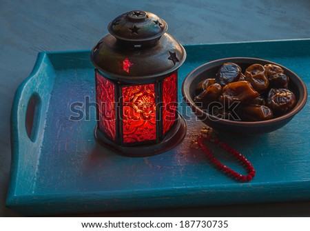 Ramadan lamp and dates on a wooden tray - stock photo