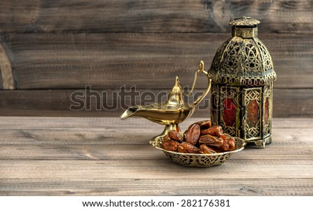 Ramadan lamp and dates on wooden background. Festive still life with oriental lantern - stock photo