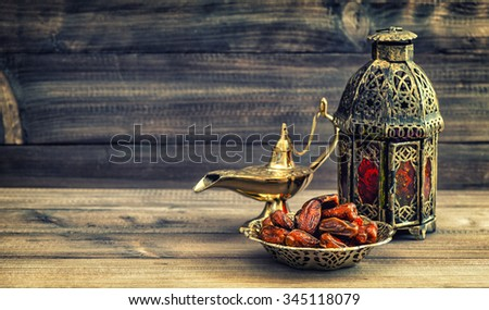 Ramadan lamp and dates on wooden background. Still life with oriental lantern. Vintage style toned picture - stock photo