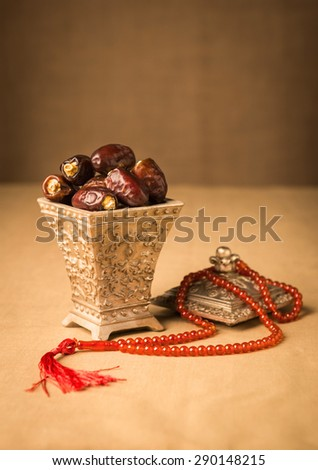 Ramadhan objects. Ripen dates in a decorative Islamic jar and prayer beads. - stock photo
