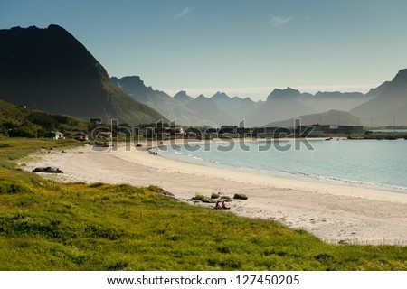 RAMBERG, NORWAY - JULY 5: Two tourists enjoying the summer weather in northern Norway on July 5, 2011 at the beach in Ramberg, Lofoten. Ramberg attracts tourists due to it's famous arctic white beach.