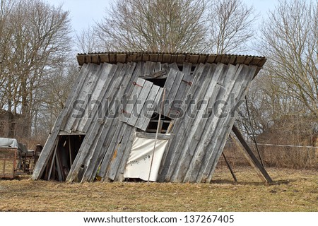Ramshackle wooden barn tilted to the side - stock photo