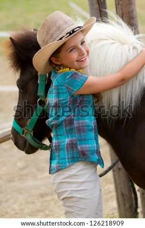 Ranch - Lovely girl with pony on the ranch - stock photo
