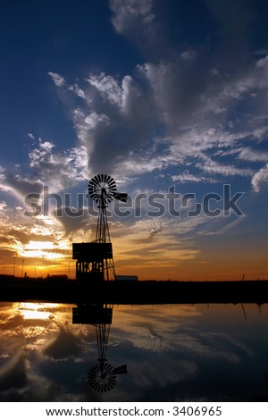 Ranch Windmill Reflected in Farm Pond, Silhouetted Against Dramatic Sunset - stock photo