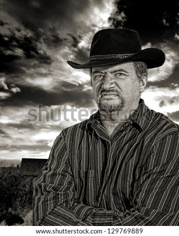 Rancher scowling with an old building with stormy sky in the background in monochrome with sepia toning - stock photo