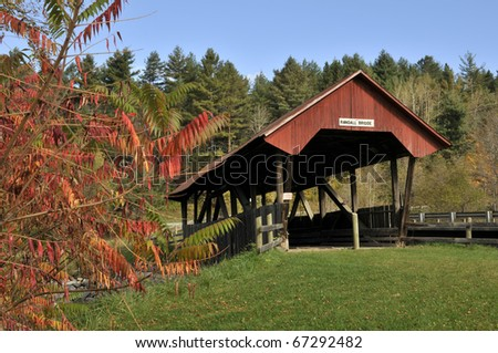 Randall Covered Bridge, Lydon, VT with Autumn Sumac in Foreground Horizontal - stock photo