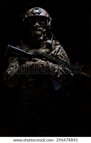 Ranger in camouflage,mask and helmet  standing with arms and looking at the camera on black background - stock photo