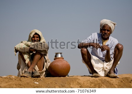 RANTHAMBORE, INDIA - CIRCA JANUARY 2007: Indian workmen stop for a water break by the roadside circa January 2007 in Ranthambore, India. - stock photo