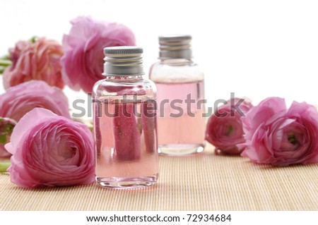 ranunculus flowers and massage lotion, on woven mat - stock photo