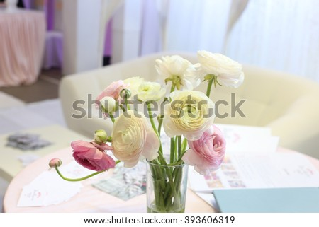 Ranunculus flowers bouquet in the glass transparent vase on the table in the studio or beauty salon. Wedding ceremony decoration and preparation, flyers in the stylish room. - stock photo