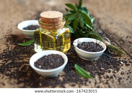 rape oil in a vessel with seeds on a wooden background - stock photo