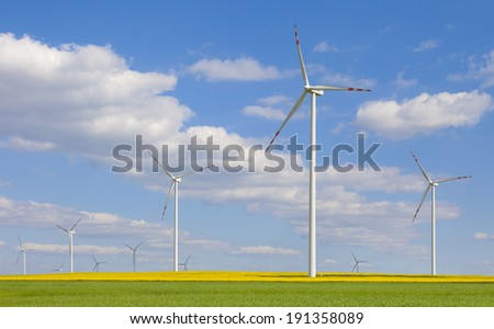 Rapeseed field with wind turbines against a blue sky - stock photo
