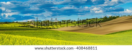 Rapeseed yellow fields in spring with blue sky and green hills,  natural eco seasonal  background, panorama - stock photo