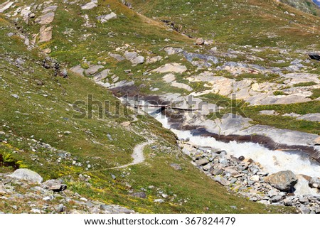 Rapid mountain stream, footpath and bridge in Hohe Tauern Alps, Austria - stock photo