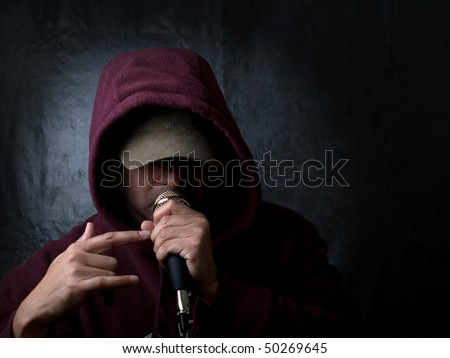 Rapper wearing hood and singing to a microphone - stock photo