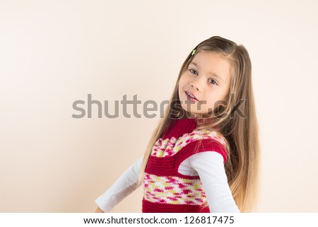 Rapunzel-like little Girl with Flowing Hair, Posing in Knitted Dress