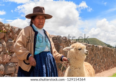RAQCHI PERU -JANUARY 15: Unidentified Quechua indian woman with lama inhabits at Raqchi Ruins, Peru on January 15, 2013. Raqchi Ruins is a popular destination for tourism from all around the world.