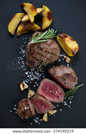 Rare beef filet mignon steak served with baked potato slices, top view