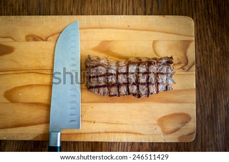 rare beef rump steak and carving knife on a wooden chopping block with a dark wood background - stock photo