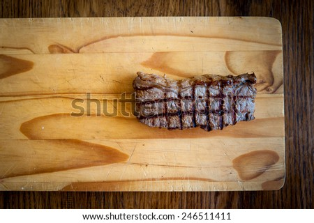 rare beef rump steak on a wooden chopping block with a dark wood background - stock photo