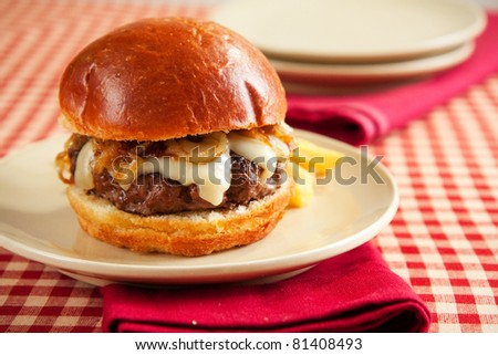 Rare cheeseburger with caramelized onions and melted swiss cheese on large roll