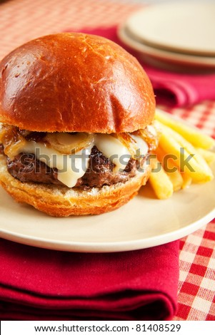 Rare cheeseburger with caramelized onions and melted swiss cheese on ...
