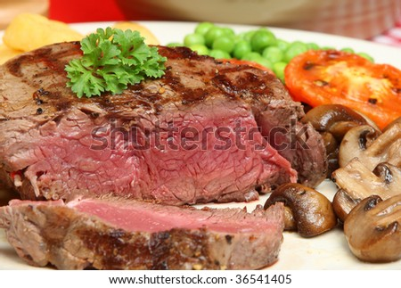 Rare fillet steak with chips, peas & mushrooms - stock photo