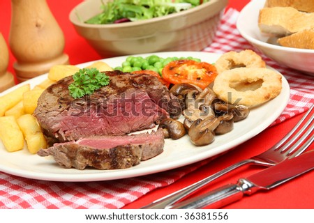 Rare fillet steak with chips, peas, mushrooms and onion rings. - stock photo